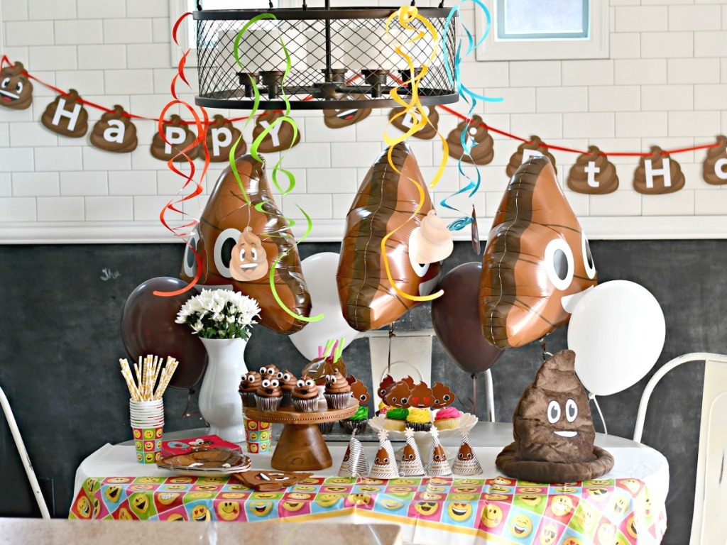 poop themed birthday party with balloons and cupcakes on table