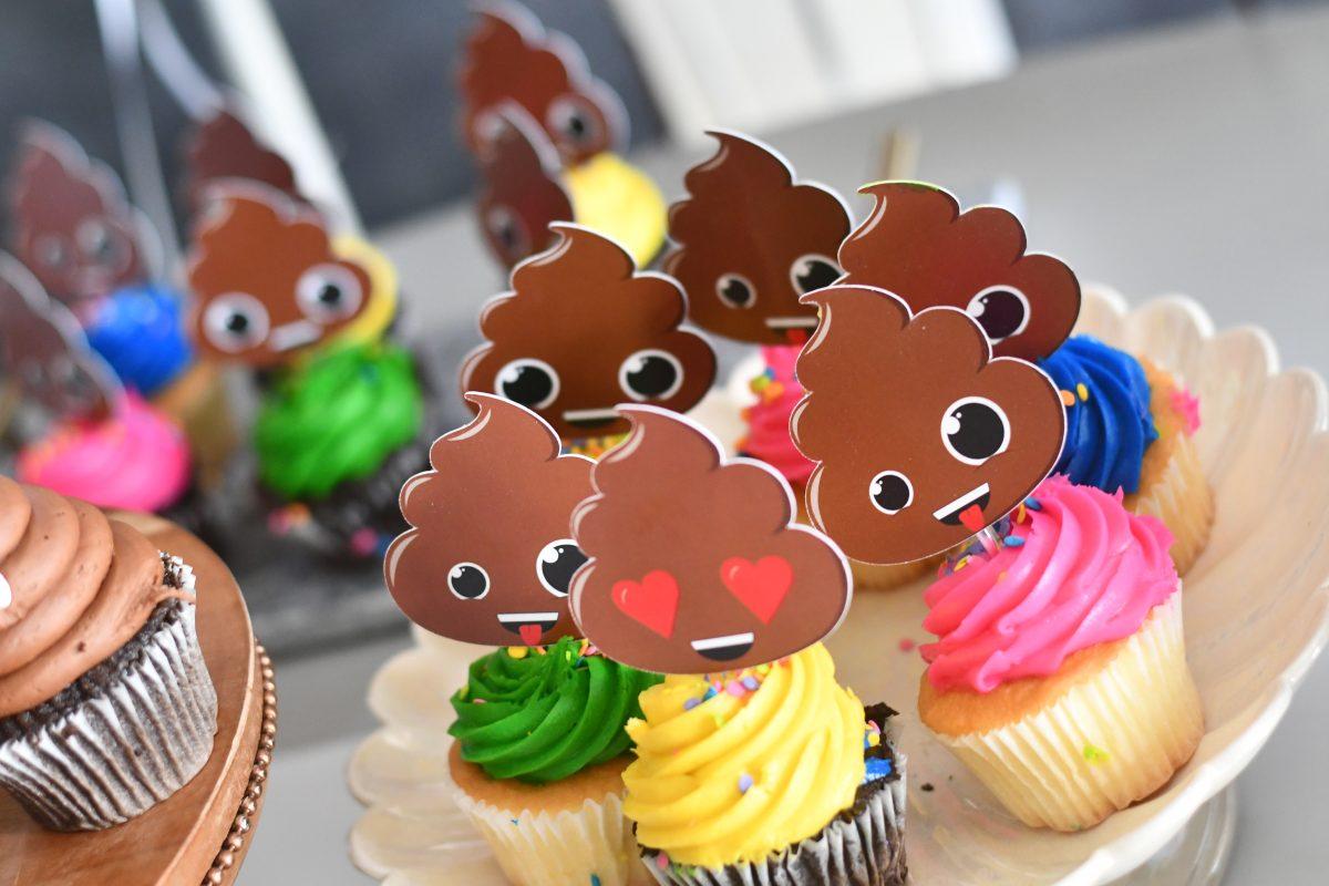 poop emoji cupcake toppers on a cake plate