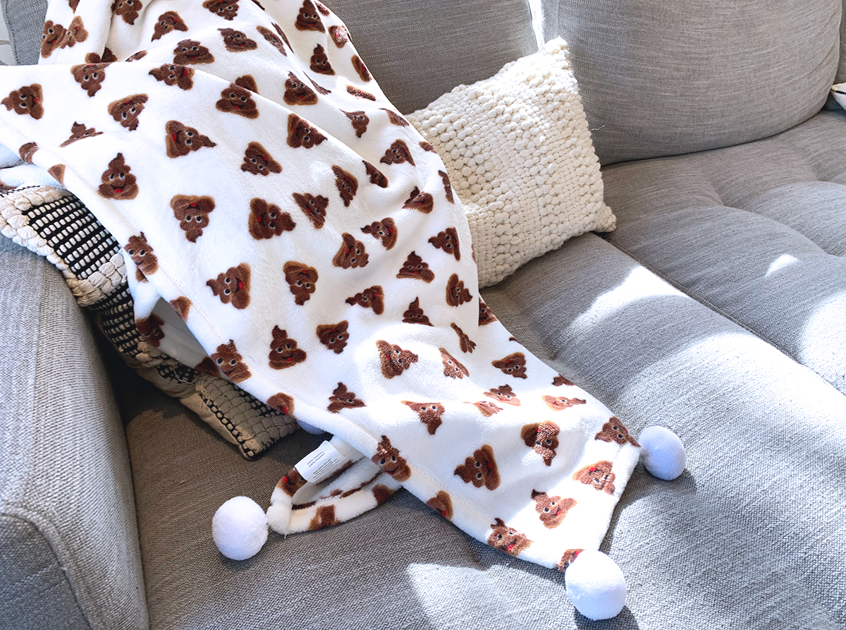 poop emoji blanket on couch